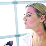"""Apply pink to the right side of your forehead, right above your brow to the hairline, on your right cheek, and then on the left cheek up to the temple, to your nose, ending at the corner of your mouth.  Make spots on your lips, chin, and jawline, then create """"bones"""" on your neck. The only spots in this makeup look that need to be perfect are your neck bones. The rest of the paint can be placed wherever you like, but I tried to copy the mural as close as possible."""