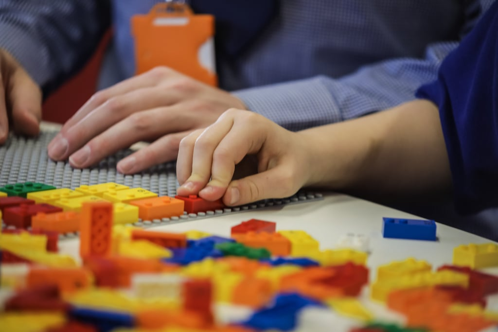 "Since their inception, Legos have played a pretty large role in many people's childhoods for obvious reasons, but now the toys are getting an update that could make them even more life-changing for children with special needs. The company is currently testing out new Lego bricks customized with bumps that could help blind and visually impaired children learn Braille. According to a release, Lego Braille Bricks will be molded with bumps that will correspond with letters and numbers in the Braille alphabet, but they'll still remain compatible with regular Lego pieces. The new bricks were first proposed to the Lego Foundation in 2011 by the Danish Association of the Blind, and they were finally unveiled on April 24 during the Sustainable Brands Conference in Paris. ""Blind and visually impaired children have dreams and aspirations for their future just as sighted children."" ""Blind and visually impaired children have dreams and aspirations for their future just as sighted children,"" John Goodwin, CEO of the Lego Foundation, said in a statement. ""They have the same desire and need to explore the world and socialize through play, but often face involuntary isolation as a consequence of exclusion from activities.""  Goodwin continued, ""With this project, we are bringing a playful and inclusive approach to learning Braille to children. I hope children, parents, caregivers, teachers, and practitioners worldwide will be as excited as we are, and we can't wait to see the positive impact."" At the moment, Lego Braille Bricks are being tested in Danish, Norwegian, English, and Portuguese, with German, Spanish, and French tests coming later in the year. The final product — which will contain 250 Braille bricks covering numbers, math symbols, and the full alphabet — is set to be released in 2020 free of charge to select institutions that assist the blind and visually impaired.      Related:                                                                                                           Lego Movie World Is Now Open, and Yep, It's Awesome — See Photos of the Legoland Addition"