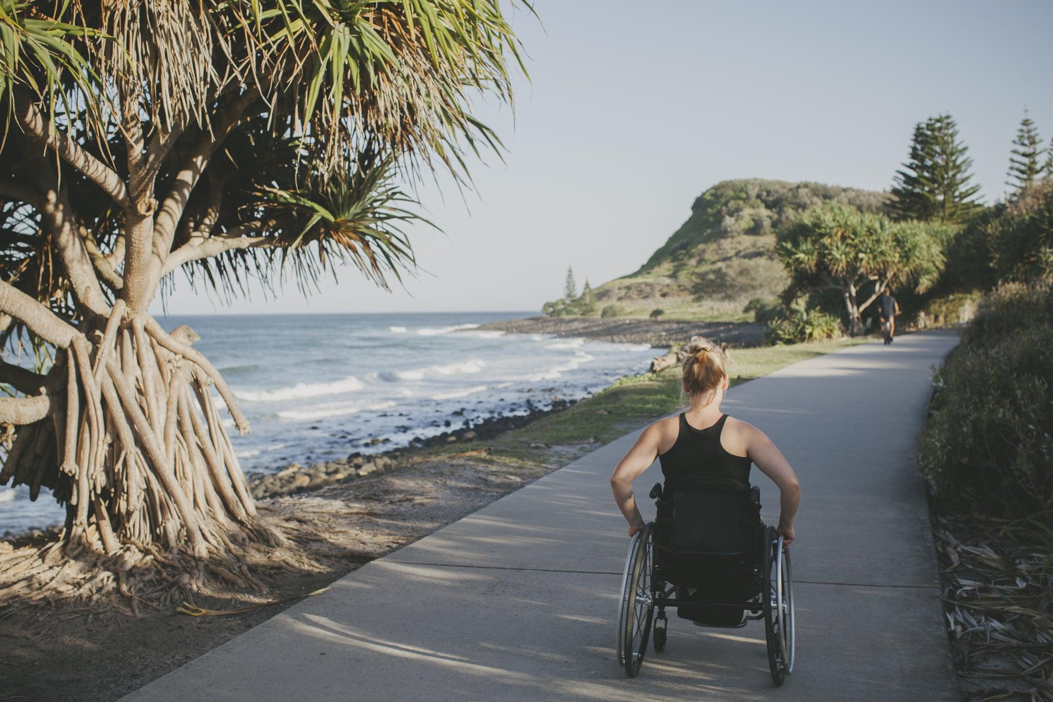 Paraplegic woman travelling in her wheelchair beside the ocean