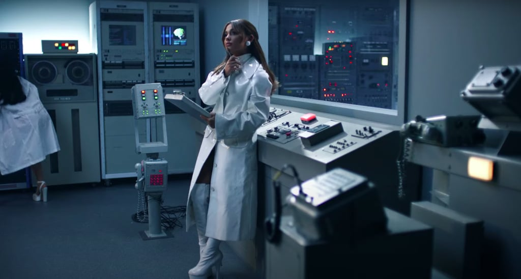 For her researcher role, Ariana went full monochrome in a white patent lab coat, over-the-knee platform boots, a turtleneck, and matching earrings.