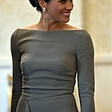 Though this dress was grey instead of navy blue and had three-quarter sleeves instead of capped ones like her prewedding getup, the draped detail on the side immediately tipped us off that it was designed by Roland Mouret. Seeing as Meghan is a known fan of buying the same clothing items in multiple different hues, we can hardly say we were surprised by her move.