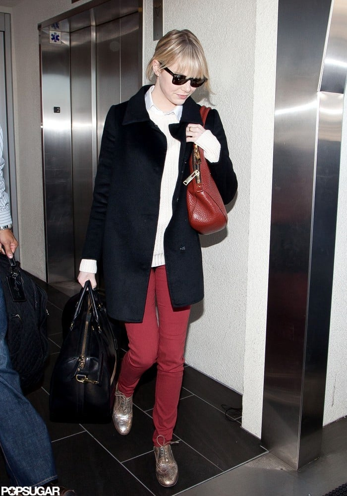 Emma Stone arrived at LAX yesterday toting a black duffle and red purse that complemented her ensemble. The actress is returning to LA after promoting her animated film with Ryan Reynolds, The Croods, in NYC last week. Their movie isn't expected to hit theaters until March, but Emma's gracing the silver screen with another good-looking Ryan very soon. She and Ryan Gosling costar in the highly anticipated Gangster Squad, opening Jan. 11.  The new year also reunites Emma with her leading man, Andrew Garfield, when production begins on The Amazing Spider-Man 2. The first installment of the franchise took the couple on a worldwide press tour that put them in the running to be named one of 2012's most stylish couples. If you think Emma and Andrew should take the title, then be sure to vote, and also check out all of our Best of 2012 coverage.