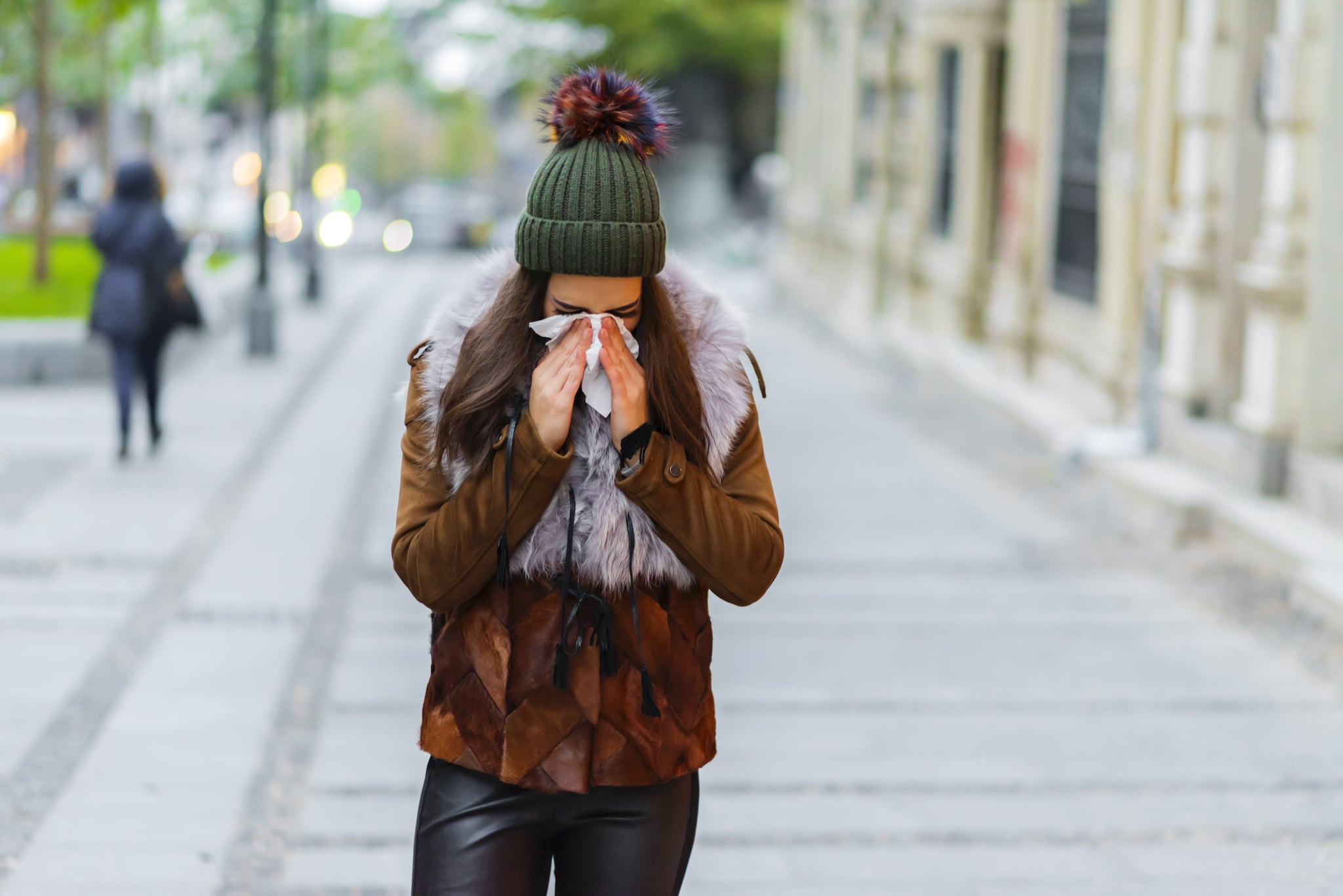 Photo of young Woman standing on the street blowing her nose. Healthcare, flu and people concept - Ill woman blowing nose to paper napkin.