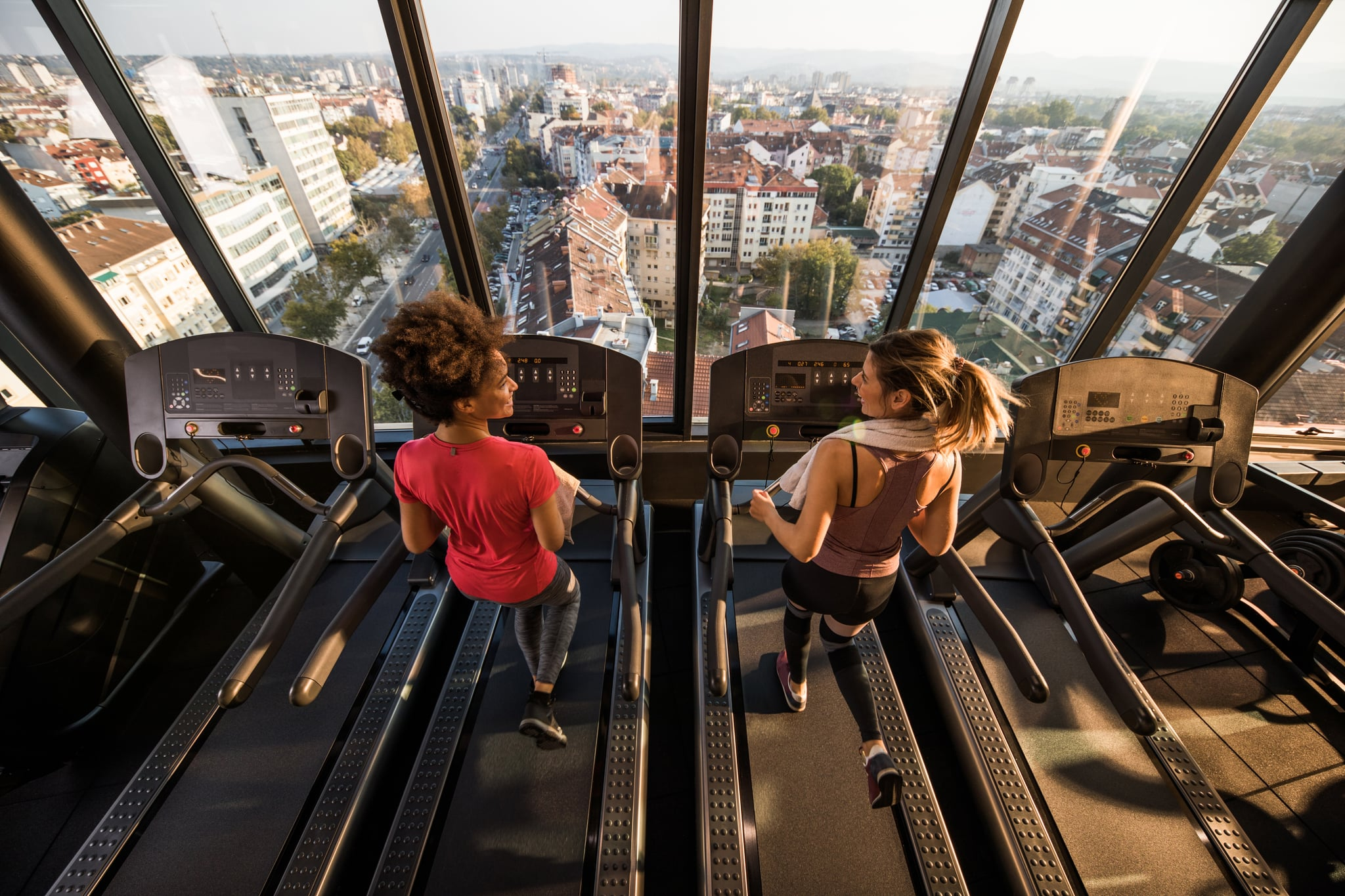 High angle view of two female athletes talking while warming up and jogging on treadmill.