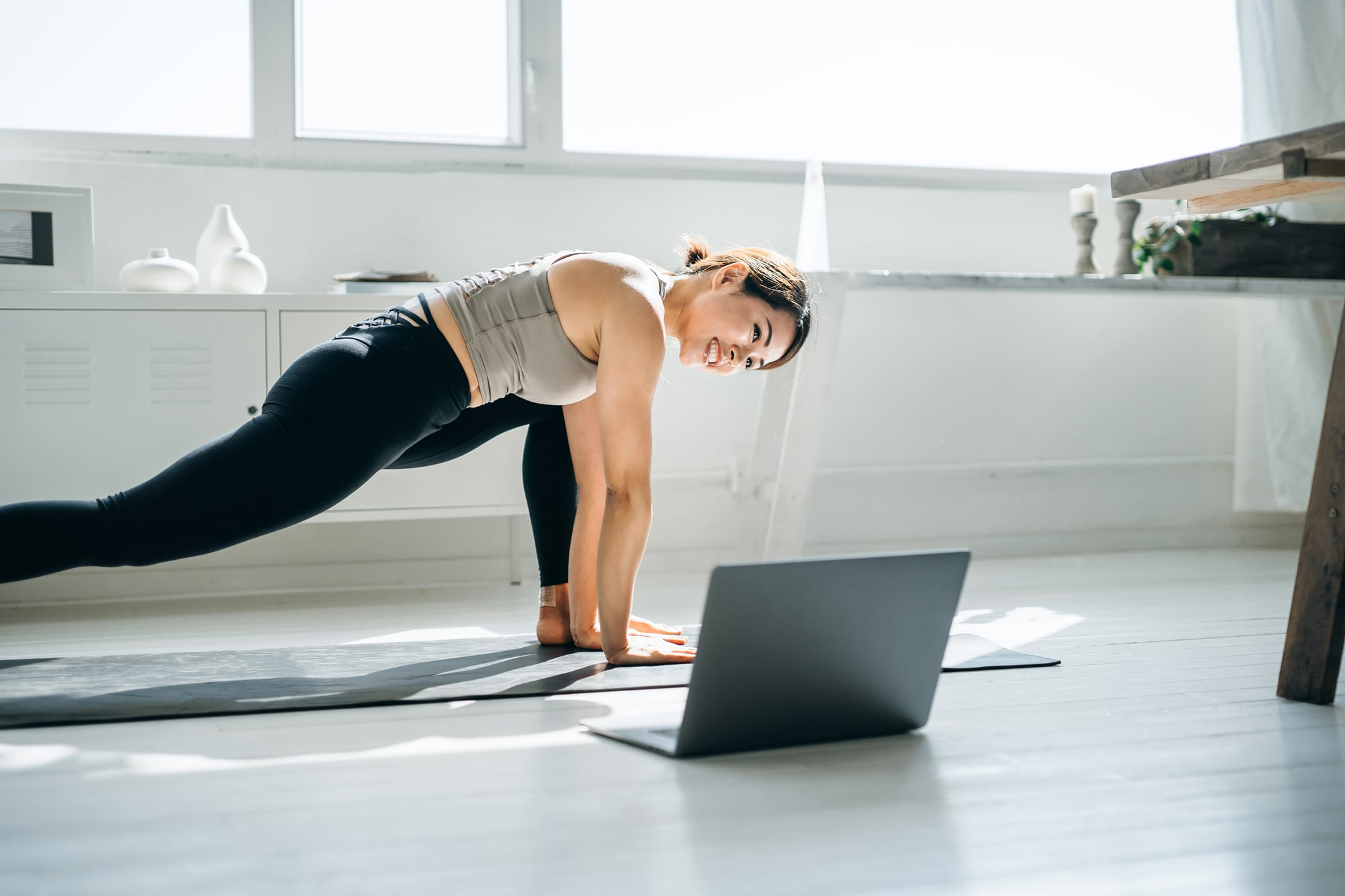 Young Asian woman doing online yoga class with laptop in the living room at home in the morning