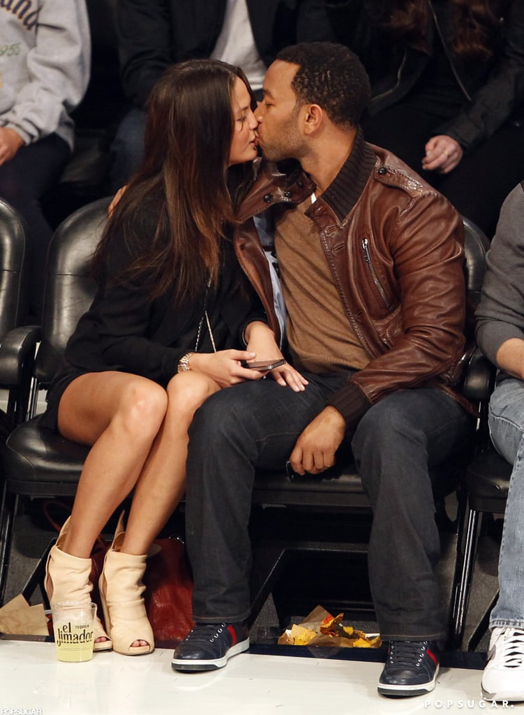 John Legend and Chrissy Teigen kept themselves occupied at a Lakers game in February 2011.