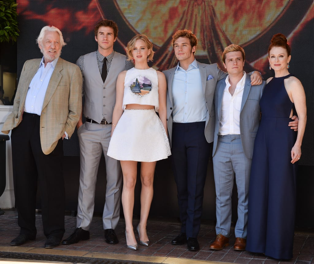 The cast of The Hunger Games: Mockingjay Part 1 — Donald Sutherland, Liam Hemsworth, Jennifer Lawrence, Sam Claflin, Josh Hutcherson, and Julianne Moore — posed for a group photo.
