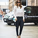 Proof that white and black — and even understated silhouettes — don't have to be boring. This showgoer pulled it all together with cool-girl shades, a pop of color on her bag, and a pair of posh pumps. Source: Le 21ème   Adam Katz Sinding