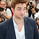 Robert Pattinson raised his eyebrows at photographers at the Cosmopolis photocall in Cannes.