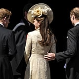 Prince William puts his hand on the back of his wife, Kate Middleton.