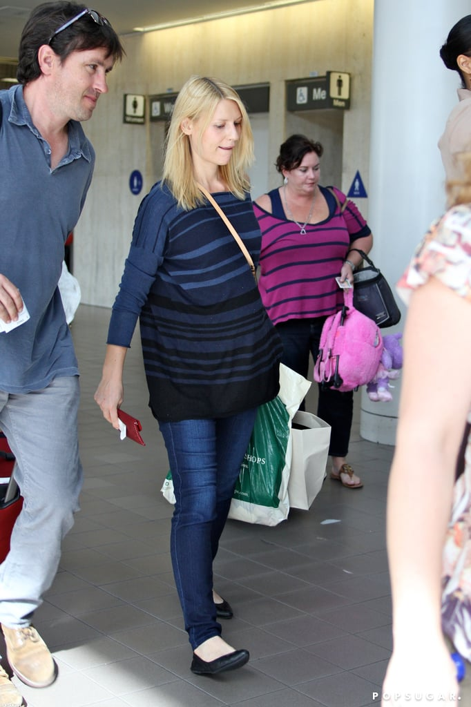 Claire Danes toted her luggage yesterday as she caught a plane at LAX. She was solo at the airport, though her husband, Hugh Dancy, was by her side over the weekend in LA. The expectant actress, who won outstanding lead actress in a drama series at Sunday's Emmy Awards for her role in Homeland, made her way through security in a casual t-shirt and jeans.  Claire wore a Lanvin gown to the Emmys to accept her award this weekend, but the individual honor wasn't the only one her critically acclaimed Showtime series snagged for its very first season. Her costar Damian Lewis won outstanding lead actor and the show also won outstanding drama. Check out our Emmys recap show for even more on the night's biggest winners, best fashion, and greatest backstage moments!