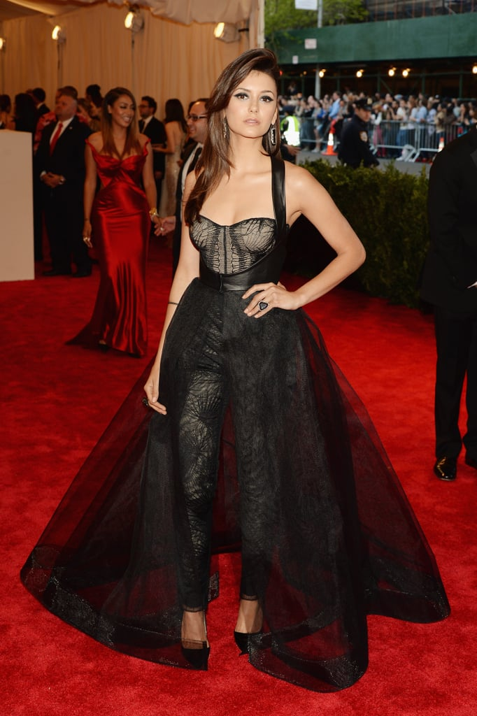 For the 2013 Met Gala, Nina Dobrev swapped her signature body-hugging creations for a custom black Monique Lhuillier jumpsuit-meets-dress. Her punk-chic ensemble composed of a corset bodice, leather harness-detail, and voluminous gauzy skirt brought attitude and intrigue to red carpet.