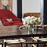 """The couple's self-described """"eclectic, rebellious, comfortable"""" style is exemplified in the living room where a rustic dining table sits in front of a mid-century modern lounger and a largescale painting. Art is the couple's biggest splurge — well, that and the giant TV that Jason insisted on purchasing!"""