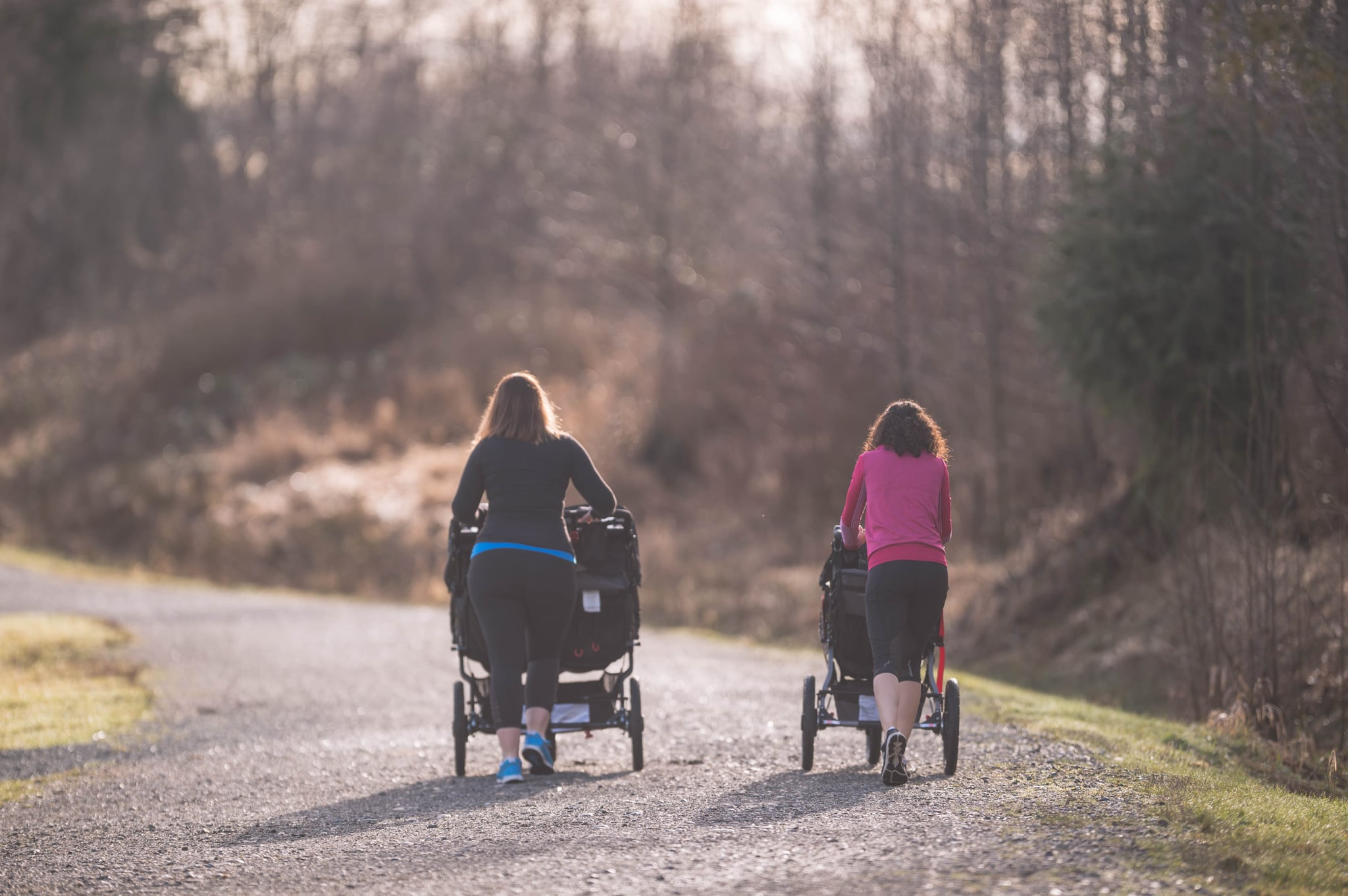 Two mothers push their young children in strollers outside. They're on a pedestrian path surrounded by trees. They are side by side and talking while they get some fresh air and exercise. The shot is from behind.