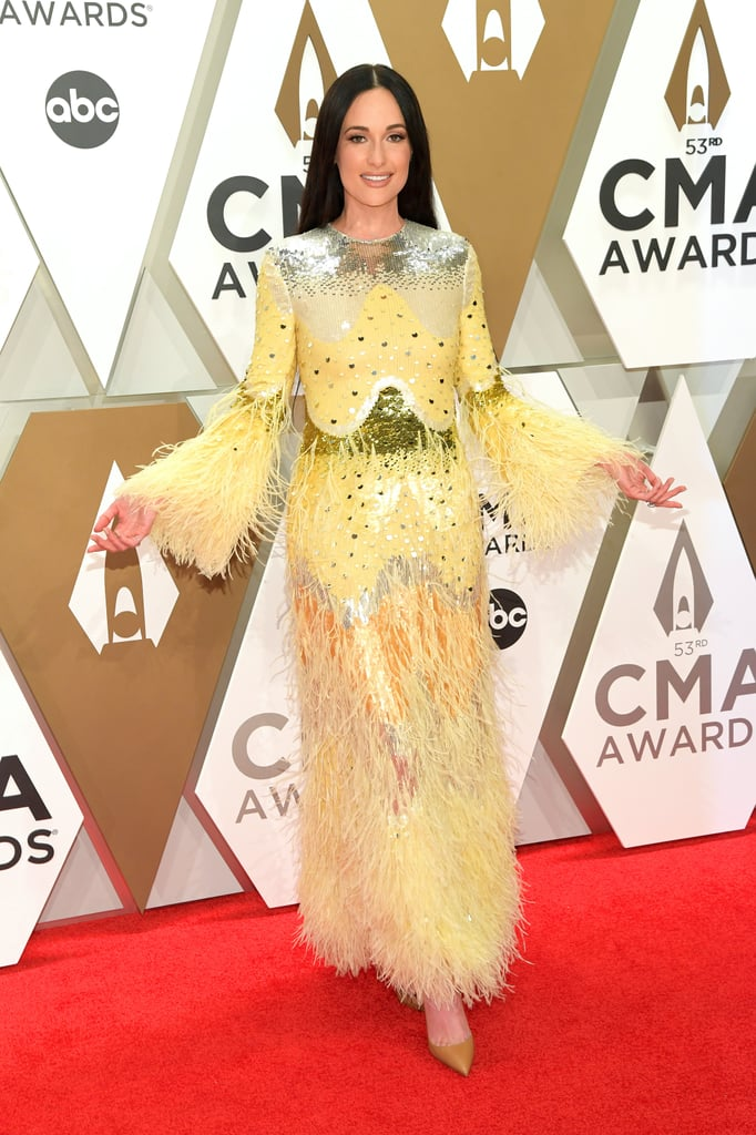 "Kacey Musgraves brought the sunshine to the CMA Awards red carpet on Wednesday night. The ""Slow Burn"" singer looked absolutely stunning in a feathery pastel yellow Valentino gown with metallic detailing. The long-sleeve ensemble perfectly complemented her pal Gigi Hadid's all-white outfit, and the two made a picturesque pair posing together for photos. Kacey's stylist, Erica Cloud, shared behind the scenes snaps of Kacey's look which helped us nail the exact details. Her dress is from Valentino's Spring Summer 2020 Womenswear line, which we last saw on the runway back in September during Paris Fashion Week. Kacey is certainly no stranger to the famed designer either — in fact, she wore a Valentino gown to the Grammys earlier this year. Looks like she's already on her way to similar luck with her CMA wins so far!       Related:                                                                                                           Yeehaw Queen? Kacey Musgraves Is More Like a Fashion Queen in These Iconic Looks"