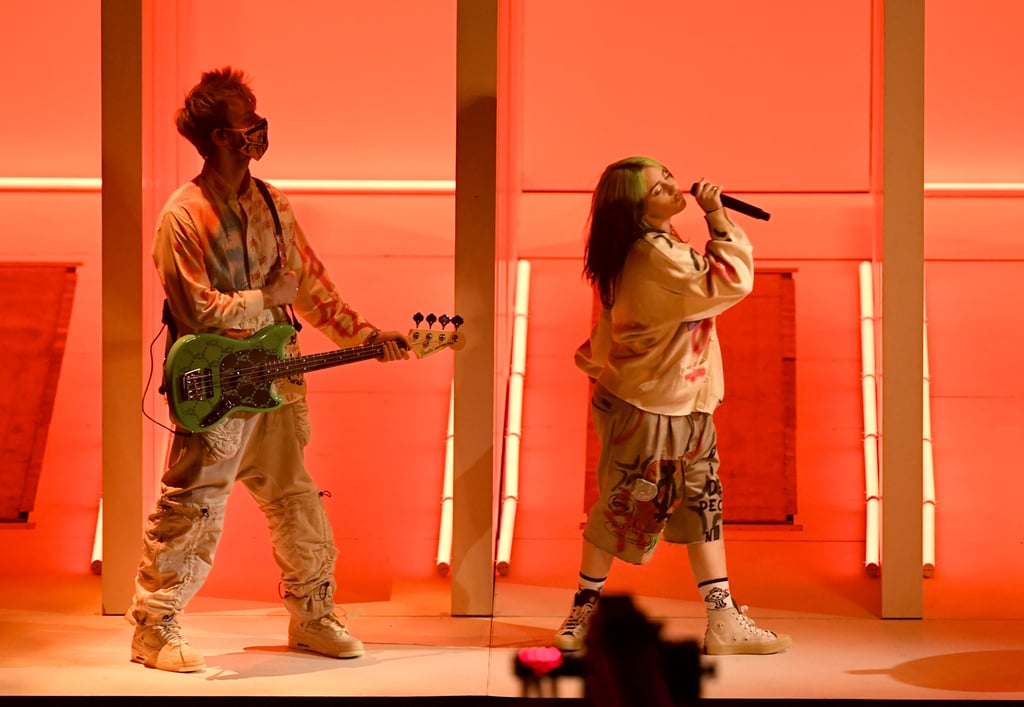 "Billie Eilish couldn't take viewers to an abandoned mall for her American Music Awards performance, so she did the next best thing: she built a mini maze on stage and brought her brother along! The ""Therefore I Am"" singer — who's nominated for two awards, including best social artist — performed her new song for the audience, keeping it simple as she walked through the series of hallways and sang along to her biting new single. The only other people on stage were a masked Finneas O'Connell on guitar and a similarly covered-up drummer.  There was a bit of an M.C. Escher moment when Billie climbed some stairs, dropped herself out a doorway, and appeared in another hallway, and it was so startling that the small audience cried out from the shock. If there were an award for the performance that left us a little shook, Billie would definitely be taking it home. Check out photos of her performance ahead!      Related:                                                                                                           Presenting the Winners of the 2020 American Music Awards"