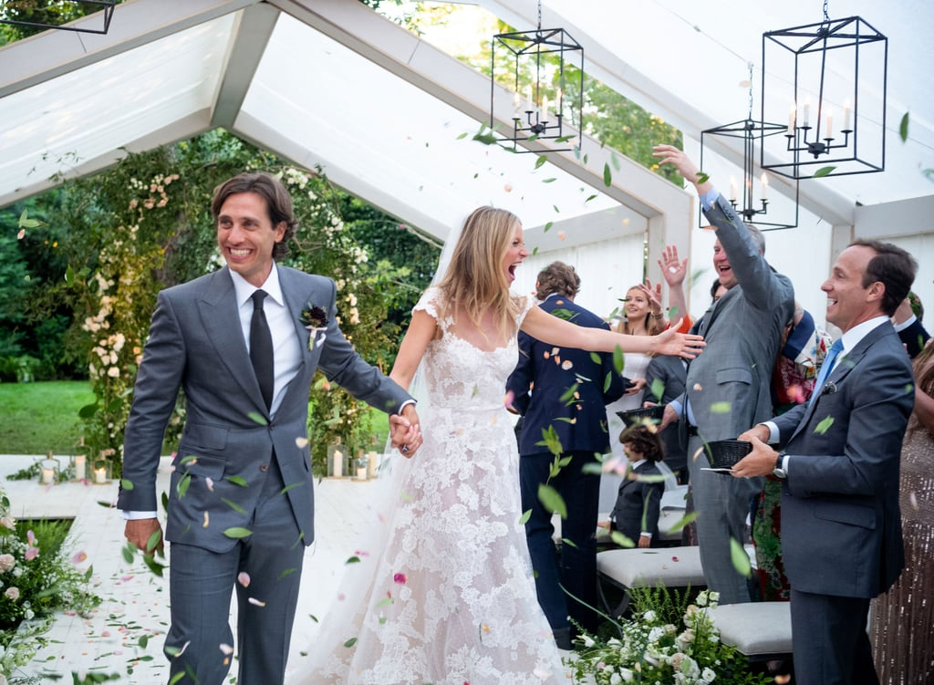 "Gwyneth Paltrow and Brad Falchuk tied the knot in a gorgeous ceremony at their Hamptons home on Sept. 29, and the actress finally gave us a glimpse of the intimate event on Friday. In a Goop article titled ""The Wedding Party: GP x Brad Tie the Knot,"" Gwyneth and Brad's Amagansett wedding is described as boasting ""perfect weather, a superlative dinner, a dance party for the ages, and a dress that defies adjectives."" Sure enough, Gwyneth stunned in an intricate lace gown by Valentino before changing into a short white Stella McCartney romper for that raucous dance party. The couple exchanged vows in front of 70 family members and A-list friends, including Gwyneth's famous mom, Blythe Danner, and Robert Downey Jr., Steven Spielberg, Cameron Diaz, and Jerry and Jessica Seinfeld, who hosted a rehearsal dinner for the couple at their own home the night before. Shortly after their nuptials, Gwyneth shared a caption-less photo of their wedding bands on Instagram. Gwyneth first met the Emmy-winning TV writer when she made a guest appearance on Glee in 2014. They went public with their romance a year later after being spotted on vacation in Italy. In 2017, Brad popped the question, and they celebrated with a star-studded engagement party hosted by Brad's longtime collaborator Ryan Murphy. ""We feel incredibly lucky to have come together at this juncture in our lives when our collective successes and failures can serve as building blocks for a healthy and happy relationship,"" they said in a joint statement. Gwyneth was previously married to Coldplay singer Chris Martin, and they have two children together, 14-year-old daughter Apple and 12-year-old son Moses, who were both by their mom's side on her big day. Brad was also previously married to producer Suzanne Bukinik, and they also have two kids, son Brody and daughter Isabella, who played roles in the wedding as well."
