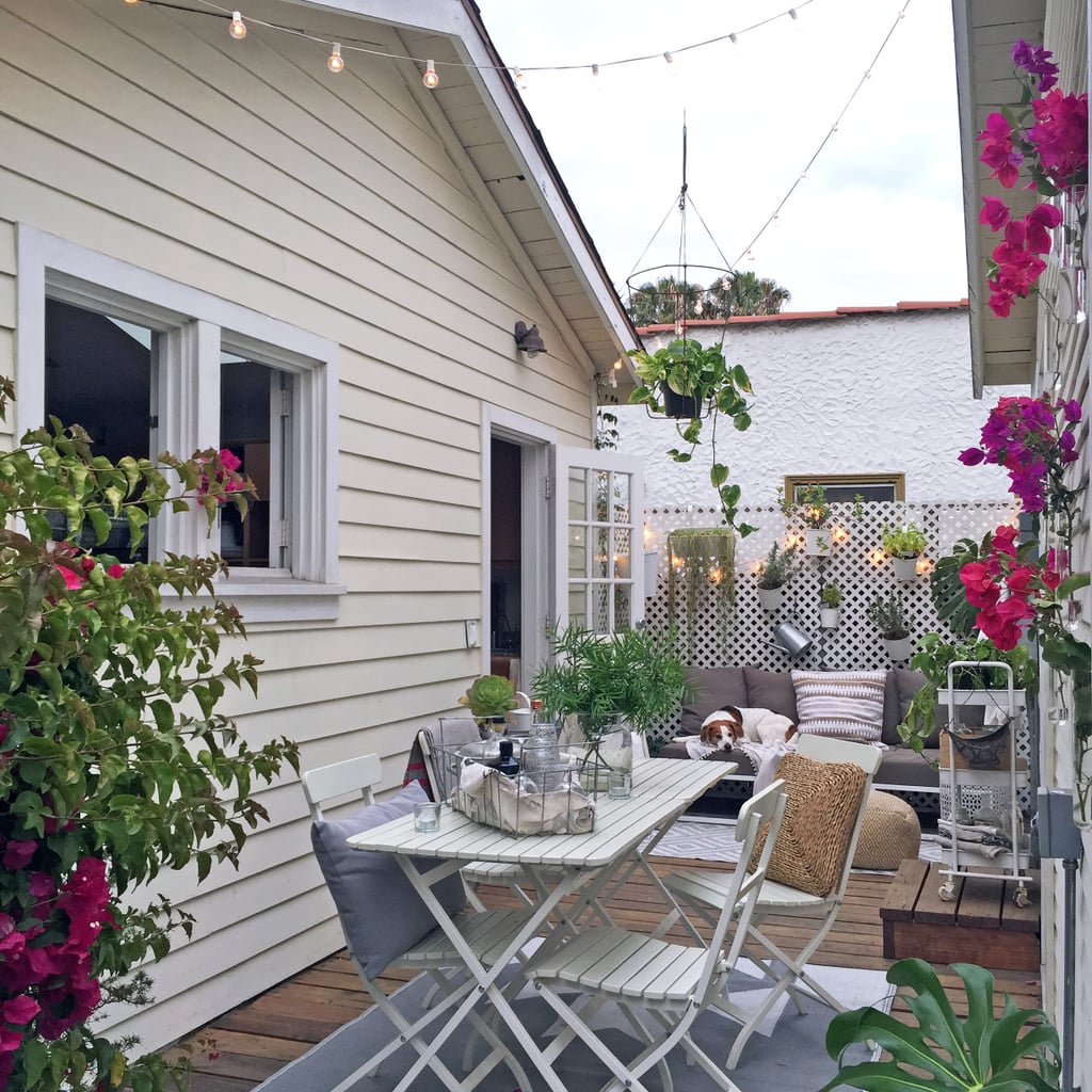 """No inch of Whitney's outdoor space is a wasted opportunity for decor or storage. """"Hang throw rugs, lanterns, serving trays, gardening tools, baskets, and more to create a lived-in ambiance, while also keeping your outdoor necessities within reach."""""""
