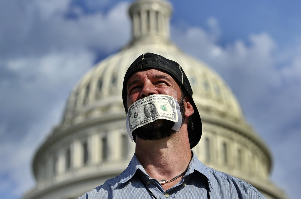 A protester put a dollar bill over his mouth during a demonstration in front of the US Capitol in Washington DC.