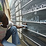 """A young girl in Léogane, Haiti, wrote on a """"Before I Die"""" blackboard, where entries from other children included """"to be president"""" and """"to make a difference in the lives of others."""" Photo courtesy of BeforeIDie.com"""