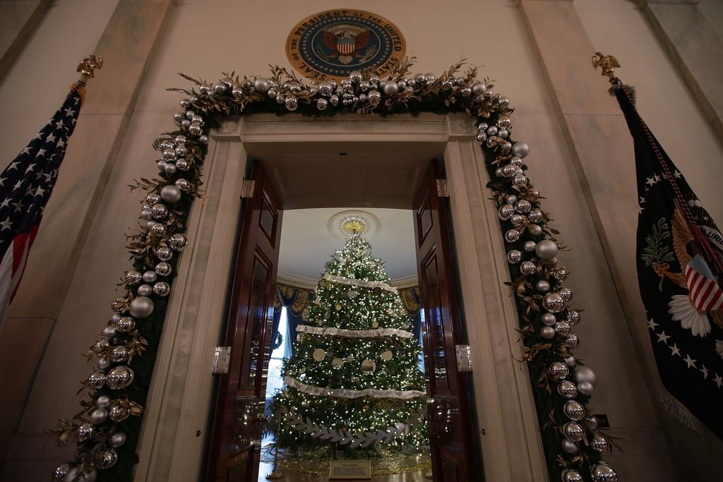 a peek of the official white house christmas tree in the blue room can be glimpsed
