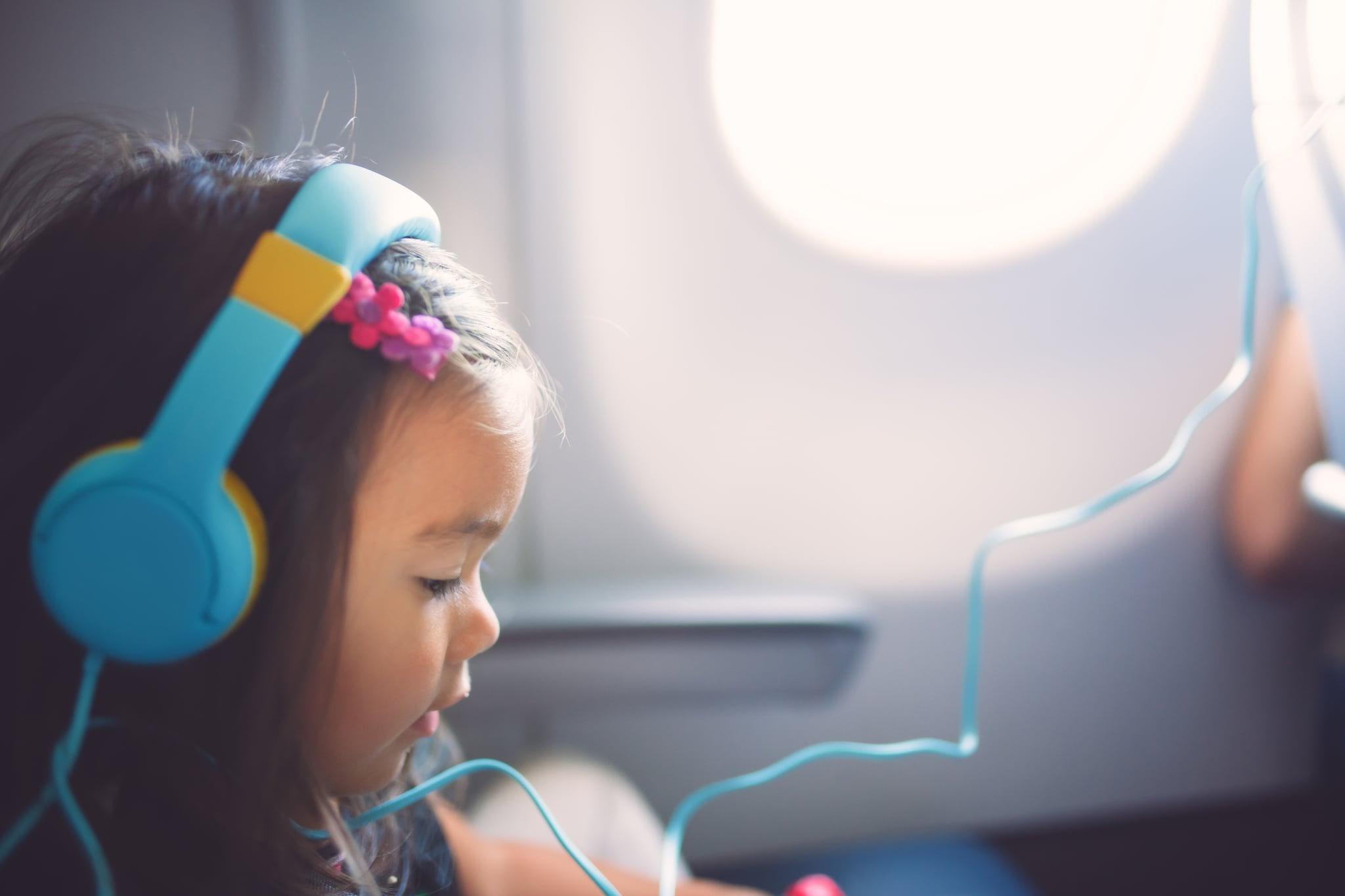 A cute 2 year old girl wearing head phones sits quietly in her seat listening to music and playing with something while flying.