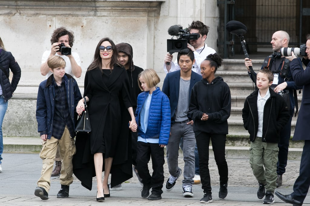 "Angelina Jolie brought her six kids — Maddox, Pax, Zahara, Shiloh, Vivienne, and Knox Jolie-Pitt — to the Louvre for an afternoon of culture in Paris on Tuesday. The First They Killed My Father director bundled up in a sleek black coat and heels as she and her brood left the Hotel de Maurice before making their way to the historic museum. Before touching down in the City of Light, Angelina traveled to Zaatari, Jordan, to visit a Syrian refugee camp. While there, she held a press conference and called for a political solution to Syria's civil war, saying that ""humanitarian aid is not a long-term solution."" Between her philanthropic efforts, Angelina has also made time to hit a few red carpets and has been bringing her kids along for the fun. Earlier this month, 14-year-old Pax was her date to the Golden Globes, where Angelina avoided a potentially awkward run-in with Jennifer Aniston. Angelina also brought daughters Shiloh and Zahara to the National Board of Review Awards gala, where they matched in all-black outfits."