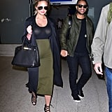 Chrissy arrived at the aiport in her signature pregnancy look, a tight skirt-and-top combo with a long duster coat and strappy sandals.