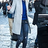 Wearing Lovers + Friends Aaron Moto Skinny Jeans with a blue sweater, gray jacket, and a pair of brogues.
