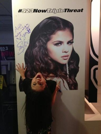 Selena Gomez stopped by a radio station and got silly with her own poster. Source: Twitter user selenagomez
