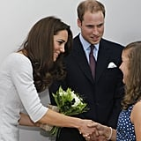 Kate shakes a young girl's hand at the center's opening ceremony.