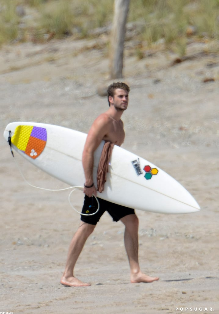 Shirtless Liam Hemsworth carried his board in Costa Rica.