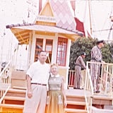 Disneyland employees were decked out in striped uniforms behind guests posing in front of an attraction.