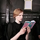A model read a book backstage ahead of a 2007 fashion show in Paris.