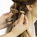 Use your fingers to tug apart and fatten up the base of the ponytail. This is called pancaking, and it will result in a softer, wider faux-braid. Plus, it makes the elastic band practically invisible.