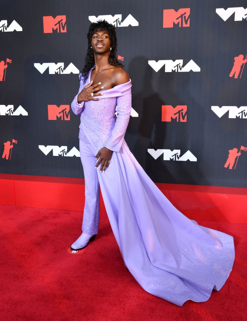"""As one of the first people on the MTV VMAs red carpet, Lil Nas X immediately had heads turning. The 22-year-old rapper showed up to the big event at the Barclays Centre wearing a stunning lilac pantsuit with a matching train that draped with every step he took. The off-the-shoulder jacket is covered with shining embellishments that are also featured throughout the leg of his pants. We cannot talk about this outfit without discussing the square toe boots he is rocking in the exact same lilac colour. Obsessed! """"I'm happy, I look good,"""" he said during the VMAs pre-show, and we couldn't agree more. It's a big night for Lil Nas X as he gears up for the release of his album Montero on Sept. 17. Not only is he performing his hit single """"Industry Baby"""" with Jack Harlow, but he is nominated for five awards tonight. """"This is going to be one to remember,"""" he said. Check out the photos of Lil Nas X in his perfectly pastel pantsuit at the VMAs ahead.      Related:                                                                                                           The MTV VMAs Red Carpet Is So Upbeat, the Fashion Alone Will Make You Get Up and Dance"""