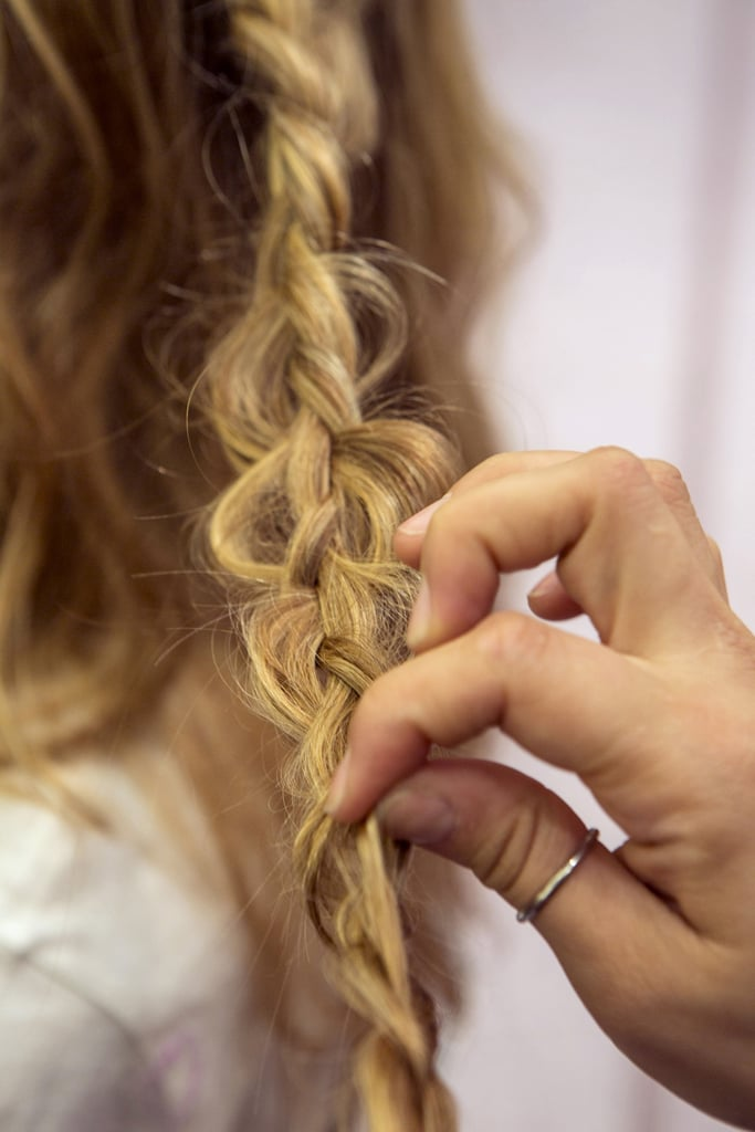 Once you've secured the braid with a clear elastic, go back and pull sections of hair within the braid to create loops in the look.