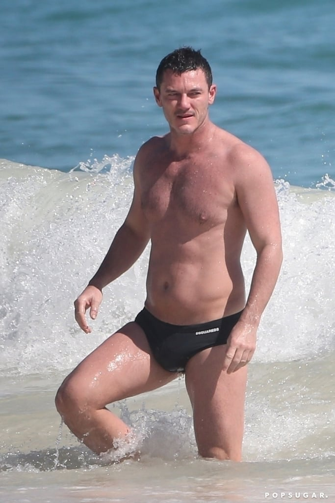 """Luke Evans is finally getting the R&R he deserves! The 39-year-old actor has been busy filming his new project Midway, and he recently took a break to escape to Tulum, Mexico with his friends. On Sunday, Luke showed off his muscular body when he hit the beach in a tiny black speedo with the word """"ICON"""" written on the back. Between his perfectly chiseled abs and strong pecs, """"ICON"""" is definitely right.  Luke is set to play Lieutenant Commander Wade McClusky in the World War II action movie, which also stars Nick Jonas, Woody Harrelson, and Mandy Moore. The film is based on the true story of the Battle of Midway and hits theatres next year.       Related:                                                                                                           Every Single, Magical Time We've Heard Luke Evans Sing"""
