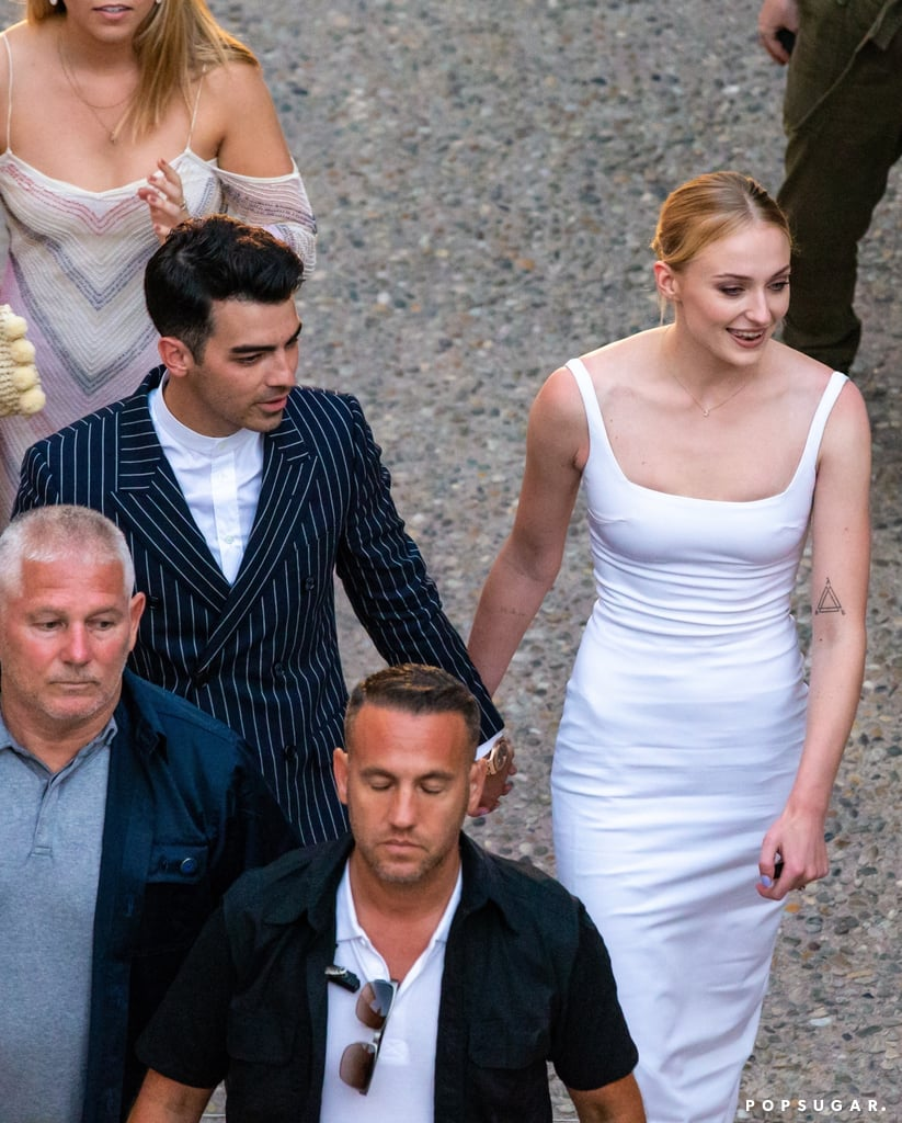 Sophie Turner and Joe Jonas are getting ready to tie the knot in France, and we can barely contain our excitement. On Thursday afternoon, the gorgeous couple were spotted arriving at the Hotel Crillon le Brave for a prewedding party. Joe dressed sharp in a navy pinstripe suit, while Sophie donned a formfitting white gown and sleek bun. The pair looked completely blissful as they made their way out of their party van and held hands. Sophie just couldn't stop smiling at her husband! Priyanka Chopra even shared a cute snapshot of her and Nick at the party on Instagram.  The following day, they celebrated with another dinner bash at Hotel de la Mirande. Joe and Sophie wore matching red ensembles for the special occasion, while the guests — including Ashley Graham, Justin Ervin, and Kevin and Danielle Jonas — wore all white.  The couple first tied the knot in May during a surprise Las Vegas wedding, but they are set to get married again this weekend. This time around, Sophie and Joe will have all of their family and friends by their side. Earlier this week, Kevin and Nick were spotted hanging out poolside at their wedding venue, while Sophie's Game of Thrones costar and maid of honor, Maisie Williams, was spotted arriving with the rest of the guests. See all the lovely pictures from Sophie and Joe's wedding bash ahead.       Related:                                                                                                           Joe Jonas and Sophie Turner's First Year as Newlyweds Is Already Off to a Cool Start