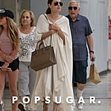 Angelina went on a shopping trip with her children, wrapping herself in an oversize shawl and toting her Saint Laurent accordion bag. She struck a neutral chord by slipping into Gianvito Rossi crisscross flats.