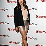 Mila Kunis wore gold shorts and a black blazer to CinemaCon in Las Vegas.