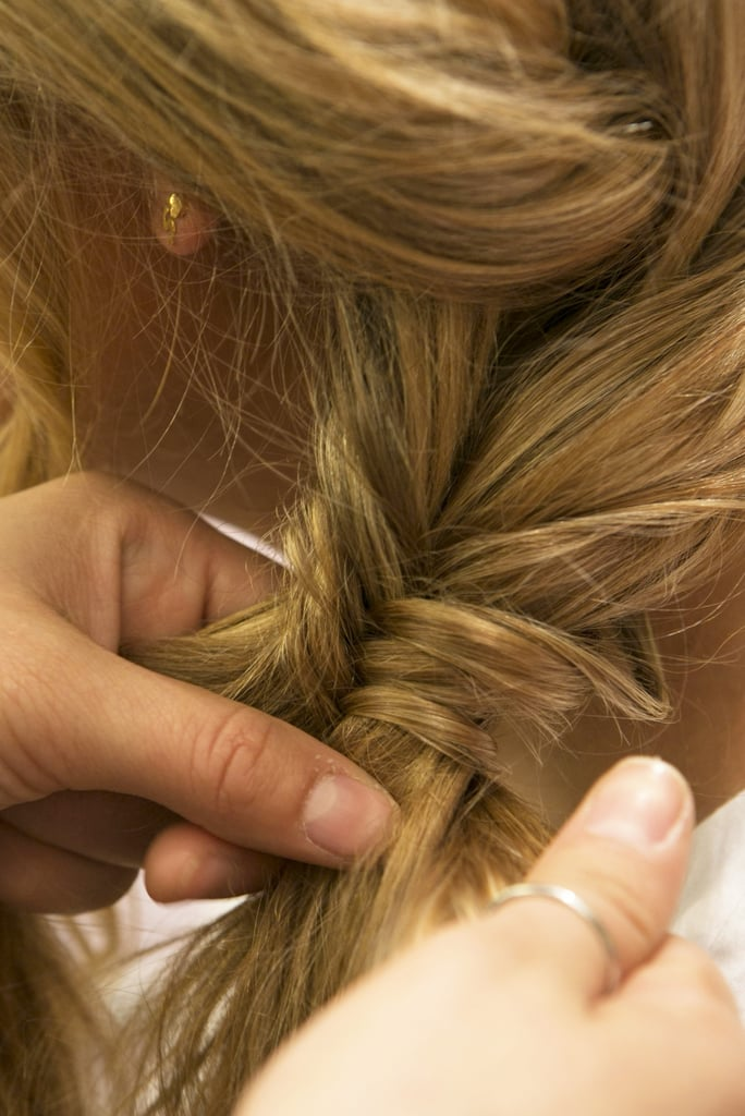 Create the fishtail braid by separating the hair into two large sections. Pull a thin strand of hair from underneath the left section and cross it over to the right section. Next, take a thin strand from the right section and cross it over to the left section, which creates the braided look.