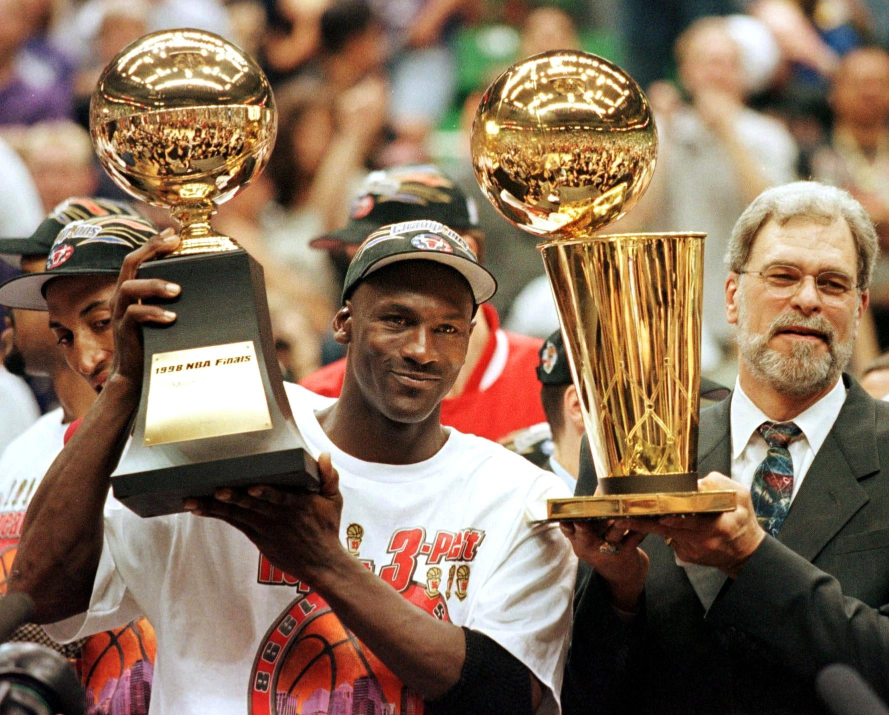 (FILES) In this 14 June 1998 file photo, Michael Jordan (L) holds the NBA Finals Most Valuable Player trophy and former Chicago Bulls head coach Phil Jackson holds the NBA champions Larry O'Brian trophy 14 June after winning game six of the NBA Finals with the Utah Jazz at the Delta Centre in Salt Lake City, UT. The Bulls won the game 87-86 to take their sixth NBA championship. Jackson left the Bulls following the 1998 season and 12 January reports indicate that Jordan plans to announce his retirement at a 13 January news conference in Chicago.   AFP PHOTO/FILES/Jeff HAYNES (Photo by JEFF HAYNES / AFP) (Photo by JEFF HAYNES/AFP via Getty Images)