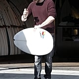 Liam Hemsworth carried a surfboard in LA.