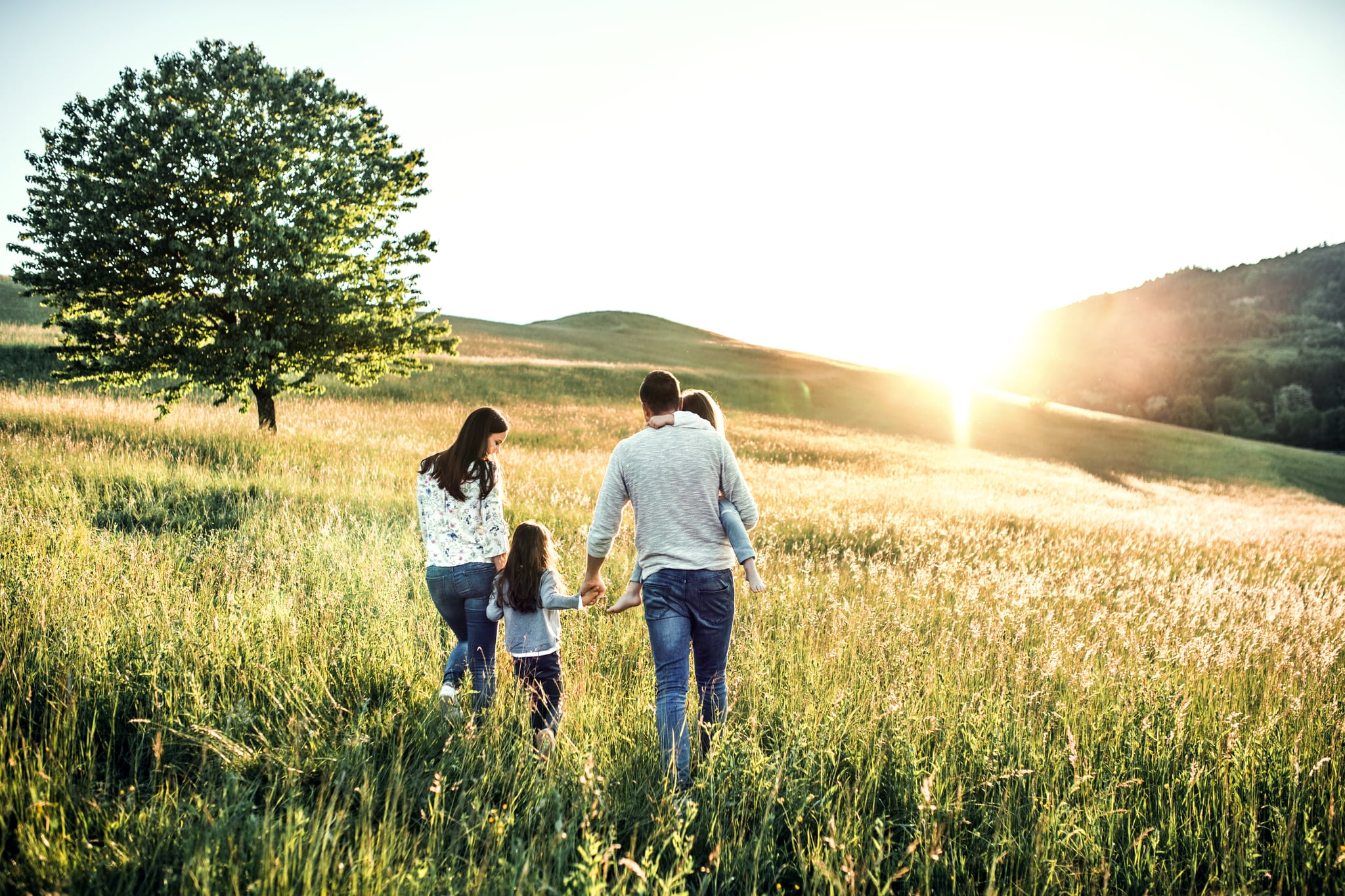 A young father and mother with their daughters on a walk on a meadow.