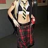 Gwen styled her layered tops — tuxedo vest, netted tank, and bikini top — with plaid parachute pants and pointed lace-up leather boots. The singer topped her already eye-catching ensemble with a straw fedora and striped tie in 2003.
