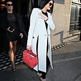 Kylie, on the other hand, looked pretty covered up in her long white and black jacket and carried a structured red bag earlier in the night.