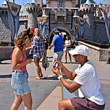 Jordan getting down on one knee in front of Sleeping Beauty's castle.