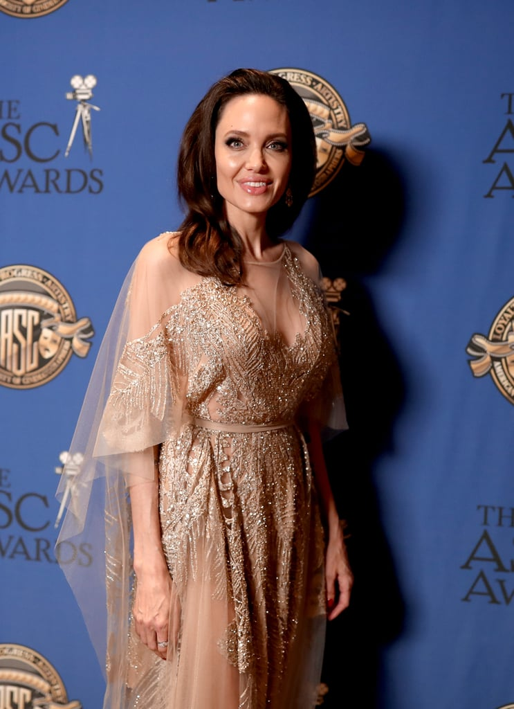 Angelina Jolie's radiant glow was undeniable at the 2018 American Society of Cinematographers Awards in Los Angeles on Saturday night. The 42-year-old actress turned heads at the swanky affair in a champagne-colored lace dress designed by Elie Saab. The proud mom of six was also honored for her directorial work on First They Killed My Father, taking home the coveted Board of Governors Award. The critically acclaimed historical thriller also scored a Golden Globe and Critics' Choice nomination for best foreign language film earlier this year. See more photos from her glammed night out ahead, then look back on Angelina's most scintillating looks over the years.