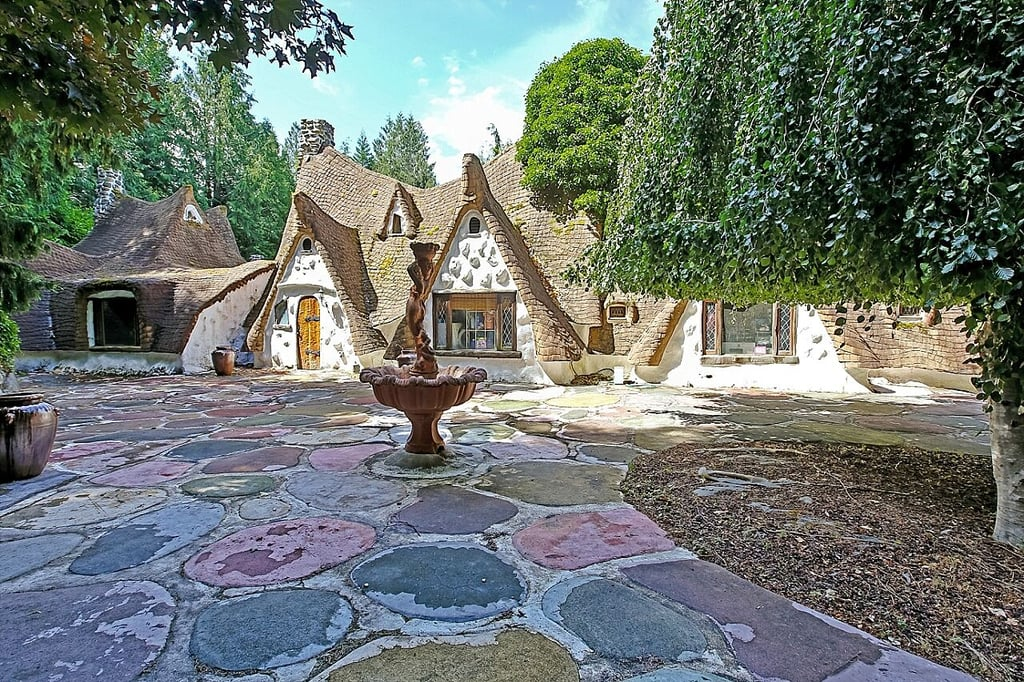 """Storybook"" doesn't even begin to describe how over the top this replica of Snow White and the Seven Dwarfs' home is. Not a single detail was overlooked in the Olalla, Washington, cottage: stained glass windows abound, the artisanal doors feature custom ironwork, wood beams are hand-carved, and walls and corners are all rounded as to be true to the fairy-tale-based movie. The home is truly a magical work of art — and it can be yours for a cool $977,000.  While there are only four bedrooms — notably not enough for each of the dwarfs to have their own sleeping quarters — the stucco property is a spacious 260 square metres and sits on a sprawling five acres thoughtfully landscaped with exotic trees. Rick Ellis of John L. Scott Real Estate holds the listing and writes that if you don't want to move in yourself, the fantastical property is prime for a bed and breakfast or wedding business. Just imagine how much guests will love walking across the whimsical stone arch bridge or peeking into the giant ""ogre's stump.""  The Kitsap Sun reports that Richey and Karen Morgan began building the home in the 1970s, meticulously crafting every detail and adding addition after addition over the decades. The current owner, Evonne Bess, bought the cottage in 2005, completed the project, and is now selling the beloved home with a heavy heart. Check out this one-of-a-kind property for yourself ahead."